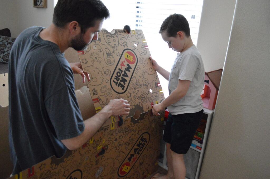 Father helping kids build a fort